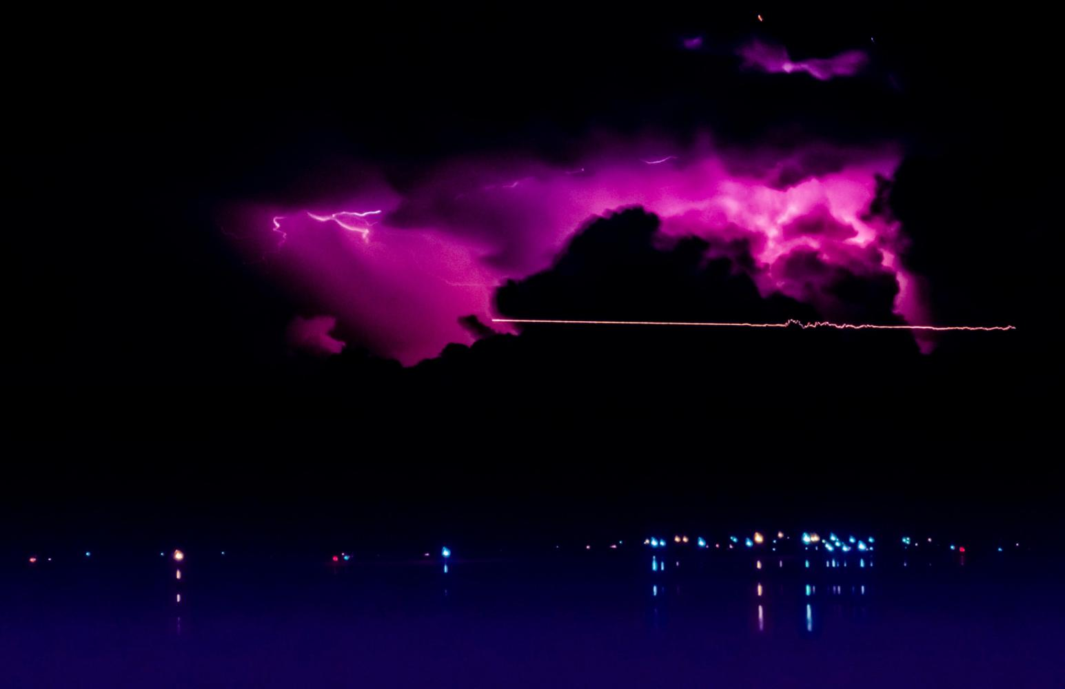 Light trail from aircraft, and distant lightning above the lights of Wellington Point. From Lota.