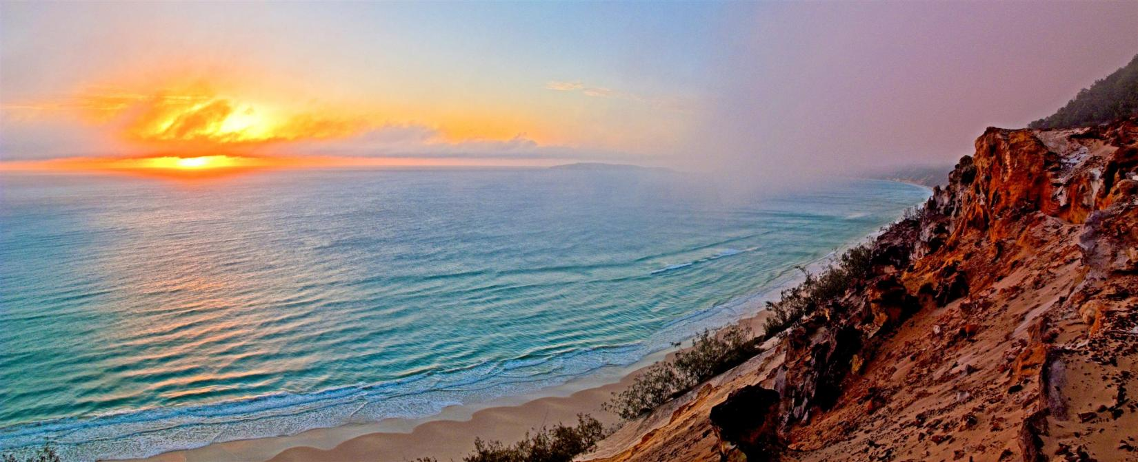 An early fog blows west onto the Pacific Ocean above the rainbow-coloured sands of Cooloola National Park.